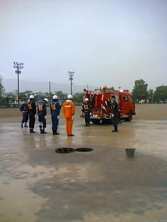 雨の中、早朝からポンプ操法大会の練習をする消防団員